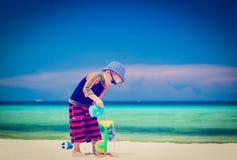 Weinig jongen die met water op zandstrand spelen Stock Foto