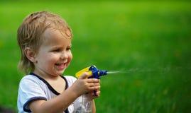 Weinig jongen die met waternevel spelen op hete de zomerdag royalty-vrije stock afbeeldingen