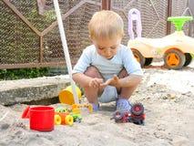 Weinig jongen die met zand speelt Stock Foto's