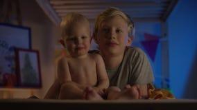 Weinig jongen die met zijn baby-broer spelen en camera bekijken stock videobeelden
