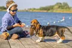 Weinig jongen die met zijn hond speelt stock fotografie