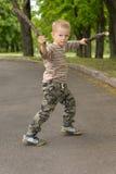 Weinig jongen die met zijn stok het vechten vaardigheden pronken stock afbeelding