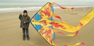 Weinig jongen die met zijn vlieger op het strand speelt Stock Fotografie