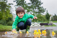 Weinig jongen, die in modderige vulklei in het park springen, rubbereenden i stock foto