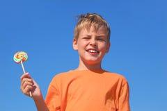 Weinig jongen die multicolored lolly houdt stock afbeeldingen