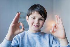 Weinig jongen die o.k. teken tonen en bij camera glimlachen stock afbeelding