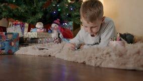 Weinig jongen die onder Kerstmisboom liggen en brief trekken aan de Kerstman stock footage