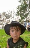 Weinig jongen die ongelukkig met een hoed kijken stock afbeeldingen
