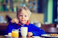 Weinig jongen die ontbijt in koffie eten Royalty-vrije Stock Afbeelding