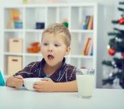 Weinig jongen die ontbijt op de vooravond van Kerstmis eten Stock Afbeeldingen