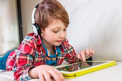 Weinig jongen die op bed leggen speelt de tablet royalty-vrije stock foto