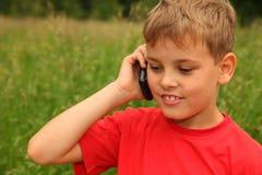 Weinig jongen die op celtelefoon in openlucht spreekt Stock Afbeeldingen