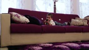 Weinig jongen die op de bank in de woonkamer en het letten op TV liggen stock video