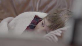 Weinig jongen die op de bank liggen die met een deken thuis wordt behandeld Het leuke kind rust De jongen is ziek, voelt hij koud stock footage