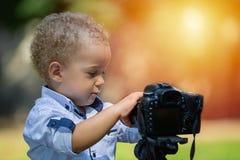 Weinig jongen die op de camera op driepoot in het park fotograferen stock fotografie