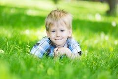 Weinig jongen die op de graslening leggen in het park stock afbeeldingen