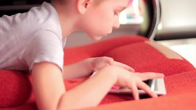 Weinig jongen die op de spelen van de tabletcomputer spelen stock video