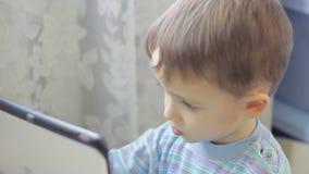 Weinig jongen die op de spelen van de tabletcomputer spelen stock videobeelden
