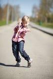Weinig jongen die op de straat in april grimassen trekken Stock Fotografie