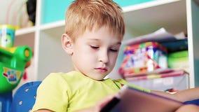 Weinig jongen die op de tablet spelen stock videobeelden