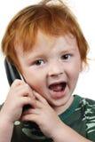 Weinig jongen die op de telefoon spreekt stock foto's
