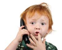 Weinig jongen die op de telefoon spreekt stock fotografie