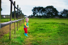 Weinig jongen die op een landbouwbedrijf spelen Stock Afbeelding