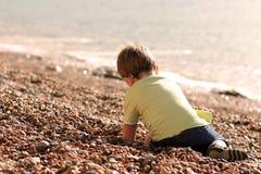 Weinig jongen die op een strand speelt royalty-vrije stock afbeeldingen