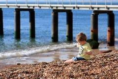 Weinig jongen die op een strand speelt stock afbeelding