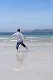 Weinig jongen die op een strand speelt stock fotografie