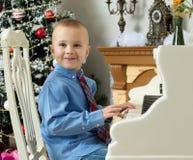 Weinig jongen die op een witte Grote piano spelen Stock Afbeelding