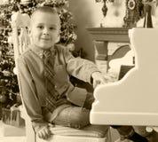 Weinig jongen die op een witte Grote piano spelen Stock Afbeeldingen