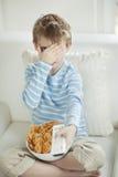 Weinig jongen die op enge film met een komhoogtepunt letten van de snackkorrels van de wielvorm Royalty-vrije Stock Foto