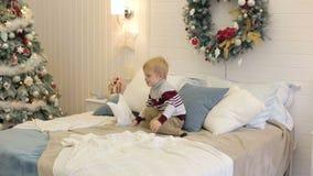 Weinig jongen die op het bed dichtbij Kerstboom springen stock videobeelden