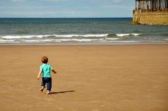 Weinig jongen die op het strand loopt Stock Foto