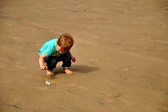 Weinig jongen die op het strand speelt stock foto