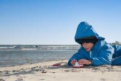 Weinig jongen die op het strand spelen Stock Foto