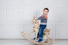 Weinig jongen die op houten paard slingeren ernstige drie-jaar-oude jongen in jeans en sweater op witte achtergrond Royalty-vrije Stock Afbeelding