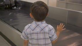 Weinig jongen die op koffer op bagagetransportband in de bagageband bij luchthaven wacht stock videobeelden