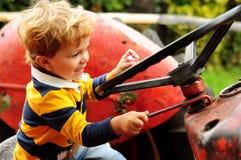 Weinig jongen die op oude tractor spelen Stock Afbeeldingen