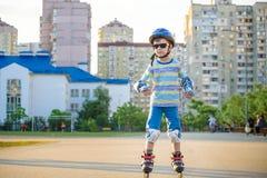 Weinig jongen die op rollen in de zomer in het Park berijden Gelukkig kind die in helm leren te schaatsen royalty-vrije stock foto