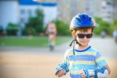 Weinig jongen die op rollen in de zomer in het Park berijden Gelukkig kind die in helm leren te schaatsen Veiligheid in sport royalty-vrije stock foto