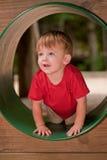 Weinig jongen die op speelplaats speelt Stock Afbeeldingen