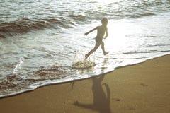 Weinig jongen die op strand naast golven binnen lopen Royalty-vrije Stock Afbeelding