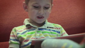 Weinig jongen die op tablet8 spelen stock video