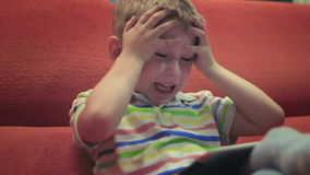 Weinig jongen die op tablet9 spelen stock footage