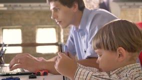 Weinig jongen die op tablet spelen wanneer zijn jonge vader die aan laptop werken, die in modern bureau zitten stock videobeelden