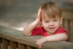 Weinig jongen die op traliewerk leunt Stock Afbeelding