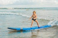 Weinig jongen die op tropisch strand surfen Kind op brandingsraad op oceaangolf Actieve watersporten voor jonge geitjes Jong geit stock fotografie