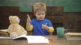 Weinig jongen die op vingers met groene bordachtergrond tellen Terug naar School Onderwijs, kinderjaren en schoolconcept stock video